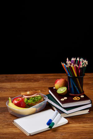 A notebook, two markers and assortment of cookies on a wooden table, copy space for text, selective focus. School lunch concept. Nutritious snack for students and kids. Healthy eating concept.