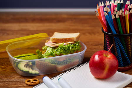 Concept of school lunch break with healthy lunch box full of sandwiches, apples and school supplies on white desk, selective focus. There is copy notepad and two markers, emphesizing the concept. Time for study and relax. Stock Photo