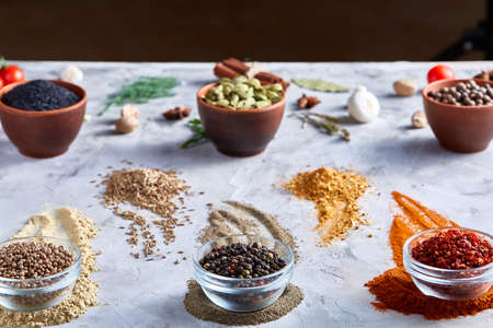 Different bowls with spices arranged in rows on white textured background, top view, selective focus. Some clipping path between them. Glass bowls with chilly, peppercorns, coriander opposite to clay bowls with cardamon and other spicies.