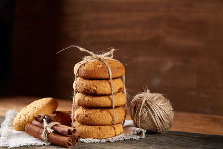 Christmas composition with pile of cookies stucked with ribbon, cinnamon sticks and dried oranges on light wooden background, close-up. Festive concept. Christmas background. Seasonal still life. Traditional Xmas composition.