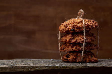 Bunch of chocolate biscuits tighted with a rope on a round wood log over rustic wooden background, close-up, selective focus. Bright gourmet sweetness. Freshly baked tasty cookies. Countryside background. Healthy eating concept.