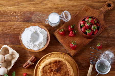 Delicious cake with fresh organic strawberries and kitchen utensils, top view, close-up, selctive focus. Sweet homemade dessert surrounded by natural ingredients on wooden table. Rustic background. Tasty morning pastry. Homemade food concept. Standard-Bild - 103191505