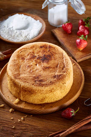 Delicious cake with fresh organic strawberries and kitchen utensils, top view, close-up, selctive focus. Sweet homemade dessert surrounded by natural ingredients on wooden table. Rustic background. Tasty morning pastry. Homemade food concept. Standard-Bild