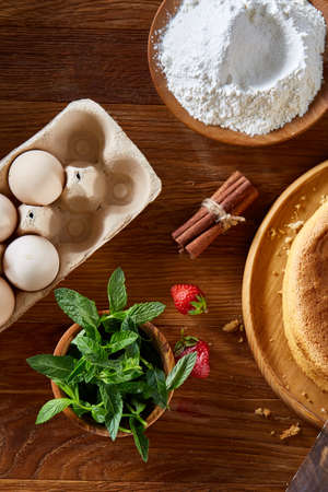 Delicious cake with fresh organic strawberries and kitchen utensils, top view, close-up, selctive focus. Sweet homemade dessert surrounded by natural ingredients on wooden table. Rustic background. Tasty morning pastry. Homemade food concept. Standard-Bild - 103191564