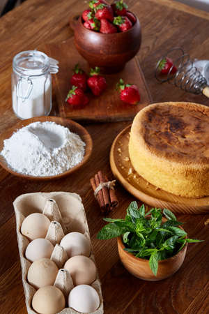 Delicious cake with fresh organic strawberries and kitchen utensils, top view, close-up, selctive focus. Sweet homemade dessert surrounded by natural ingredients on wooden table. Rustic background. Tasty morning pastry. Homemade food concept. Stock Photo