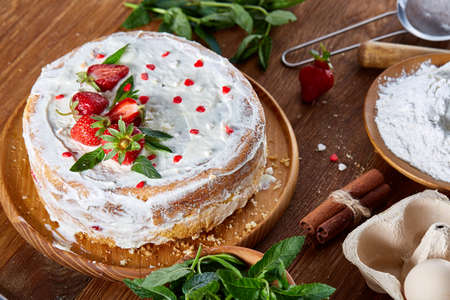 Strawberry tart covered with whipped sour cream on a wooden tray over rustic background, close-up, selective focus, shallow depth of field. Homemade bakery with fresh eggs, mint leaves, organic strawberry and flour. Food concept. Bakery background. Standard-Bild