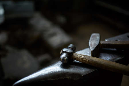Close-up of a blacksmiths hands manipulating a metal piece above his forge in the smithy, selective focus. Blacksmith striking a metallic object with his hammer. Blur pavement in background. Ancient manufacturing. Art and crafts concept.
