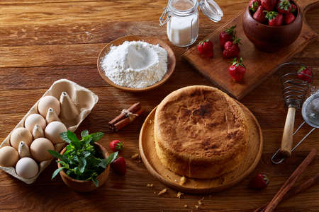 Delicious cake with fresh organic strawberries on cutting board over wooden background, top view, close-up, selctive focus. Sweet homemade dessert on wooden table. Rustic background. Tasty morning pastry. Homemade food concept. Standard-Bild - 103735577
