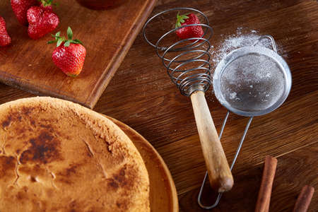 Delicious cake with fresh organic strawberries on cutting board over wooden background, top view, close-up, selctive focus. Sweet homemade dessert on wooden table. Rustic background. Tasty morning pastry. Homemade food concept. Stock Photo