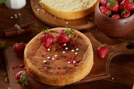 Delicious cake with fresh organic strawberries on cutting board over wooden background, top view, close-up, selctive focus. Sweet homemade dessert on wooden table. Rustic background. Tasty morning pastry. Homemade food concept. Standard-Bild - 103735592