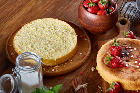 Delicious cake with fresh organic strawberries on cutting board over wooden background, top view, close-up, selctive focus. Sweet homemade dessert on wooden table. Rustic background. Tasty morning pastry. Homemade food concept. Standard-Bild - 103735591
