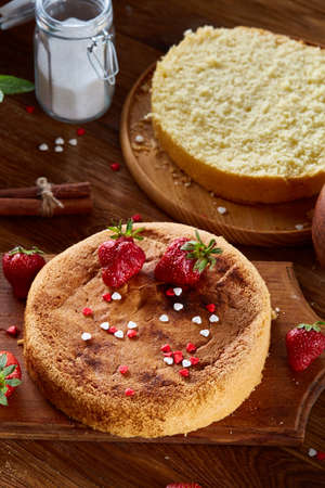 Delicious cake with fresh organic strawberries on cutting board over wooden background, top view, close-up, selctive focus. Sweet homemade dessert on wooden table. Rustic background. Tasty morning pastry. Homemade food concept. Standard-Bild