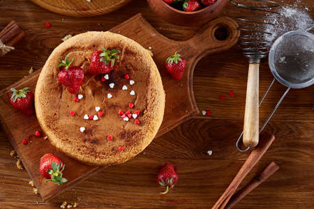 Delicious cake with fresh organic strawberries on cutting board over wooden background, top view, close-up, selctive focus. Sweet homemade dessert on wooden table. Rustic background. Tasty morning pastry. Homemade food concept. Standard-Bild - 103735594