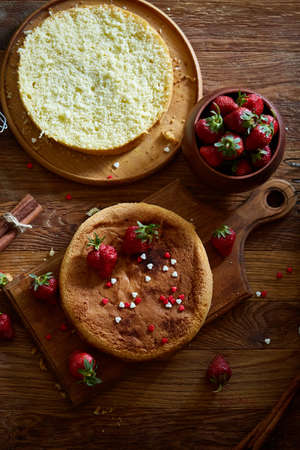 Delicious cake with fresh organic strawberries on cutting board over wooden background, top view, close-up, selctive focus. Sweet homemade dessert on wooden table. Rustic background. Tasty morning pastry. Homemade food concept. Standard-Bild - 103735605