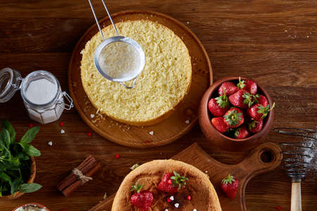 Delicious cake with fresh organic strawberries and mint, top view, close-up, selctive focus. Sweet homemade dessert surrounded by natural ingredients on wooden table. Rustic background. Tasty morning pastry. Homemade food concept.