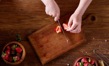 Knife in girls hand cutting a fresh strawberry on wooden table, top view, selctive focus. Preparation for cooking something delicious. Natural organic berries. Nutritious vitamin. Healthy food concept.
