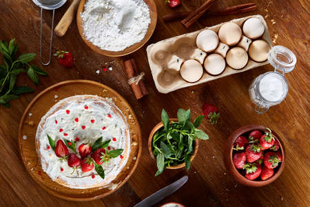 Top view raw ingredients for cooking strawberry pie or cake on wooden table: eggs, flour, sugar and strawberry, flat lay. Bakery background. Recipe for strawberry pie. Tasty morning pastry. Homemade food concept.