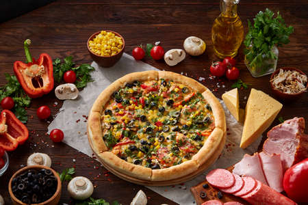 Pizza still life. Part of freshly baked Italian pizza and its components arranged on wooden background, top view, close-up, selective focus. Delicious snack. Traditional homemade Italian pizza. Mediterranian cuisine. Fast food concept.