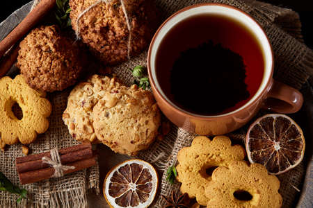Cookies with cinnamon and two cups of tea on a burlap napkin, selective focus, close-up, top view. Delicious teatime on Christmas background. Festive concept. Sweet homemade treat.