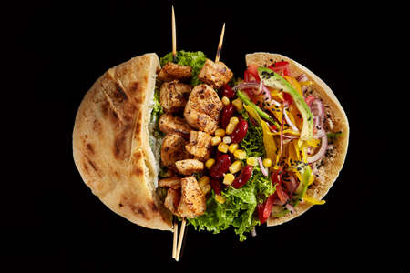 Pita stuffed with chicken, vegetables and kebab on wooden background, shallow depth of field, blurred.