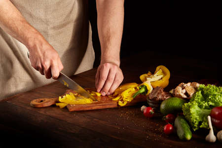 Chefs hands cutting yellow bell pepper for colorful barbecue composition on kitchen table, close-up, selective focus. Still-life on a wooden background. Delicious barbecue background. Food concept. Imagens
