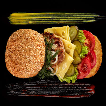 Big fresh burger with sauce arranged on black square plate on black wooden background, flat lay, close-up, selective focus. American classic burger menu. Artistic serving. Nutritious junk food. Fast food concept. Imagens