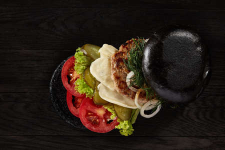 Black burger on vintage wooden background, top view, close-up, selective focus. Artistic layout. Exotic hamburger stuffed with tomatoes, letucce, onion, piccoli and cheese. Nutritious junk food. Fast food concept.