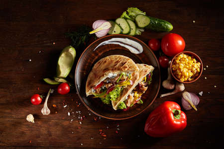 Exotic still slife with pita on an old-fashioned plate, fresh vegetables and yummy kebab over vintage wooden background, top view, close-up, selective focus. Mediterranian or Middle East cuisine. Rustic food background. Fast food concept. Imagens