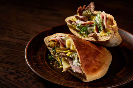 Tasty Jewish pita stuffed with grilled meat, ham, cheese, piccoli and sauce on vintage wooden background, top view, close-up, selective focus. Organic stuffed roll for delicious lunch. Traditional Middle East cuisine. Fast food concept. Imagens