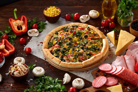 Pizza still life. Freshly baked Italian pizza and its components arranged on wooden background, top view, close-up, selective focus. Delicious snack. Traditional homemade Italian pizza. Mediterranian cuisine. Fast food concept.