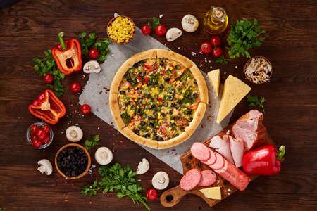 Pizza still life. Freshly baked Italian pizza and its components arranged on wooden background, top view, close-up, selective focus. Delicious snack. Traditional homemade Italian pizza. Mediterranian cuisine. Fast food concept. Standard-Bild - 104816385