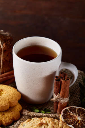 Sweet Christmas teatime with oatmeal, chocolate biscuits, cinnamon sticks and dried oranges, on rustic wooden background, close-up, selective focus. Christmas concept. Festive background.