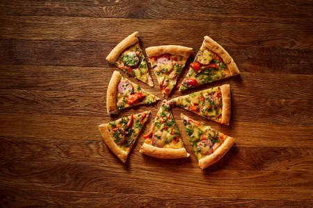 Freshly baked delicious pizza divided into slices on rustic wooden background, top view, close-up, selective focus. Some copy space for your text. Delicious snack. Yummy junk food. Traditional Italian pizza. Mediterranian cuisine. Fast food concept.