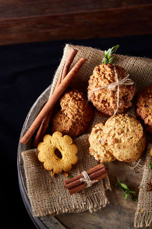 Conceptual composition with assortment of cookies, cinnamon sticks bunch and dried oranges with burlap napkin on a wooden barrel over rustic background, selective focus, close-up. Delicious treat. Relaxing teatime. Christmas background.