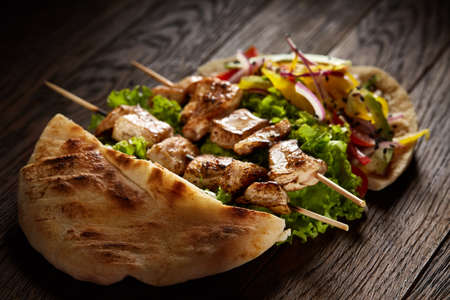 Tasty Jewish pita stuffed with grilled chicken, vegetables, letucce and kebab on vintage wooden background, top view, close-up, shallow depth of field, blurred. Organic roll for delicious lunch. Traditional Middle East cuisine. Fast food concept. Imagens