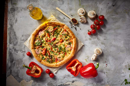 Tasty Italian pizza and its ingredients on white textured background, top view, close-up, selective focus. Delicious snack. Traditional homemade Italian pizza. Mediterranian cuisine. Fast food concept. Imagens