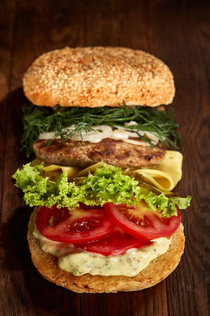Close-up of traditional american burger with lettuce, cheese, onion and tomato on wooden background Imagens