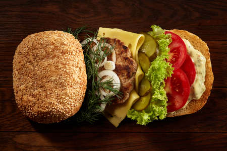 Close-up of delicious fresh home made burger with piccoli, lettuce, cheese, onion, tomato, dill and yummy beef on a dark wooden background. Traditional American hamburger. Junk food full of calories. Fast food concept. Imagens