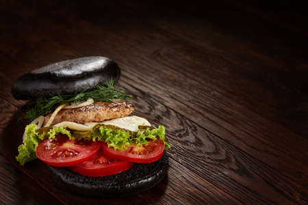 Black burger on vintage wooden background, top view, close-up, selective focus. Imagens