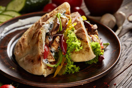 Pita stuffed with chicken, beans and letucce on clay plate over wooden background, side view, selective focus.