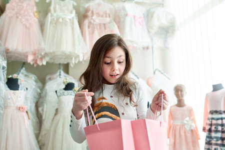 cute little girl on shopping. portrait of a kid with shopping bags. child in dress, sunglasses and shoes near shopping mall having fun. shopping Imagens - 104976183