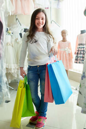 cute little girl on shopping. portrait of a kid with shopping bags. child in dress, sunglasses and shoes near shopping mall having fun. shopping Standard-Bild - 104977428