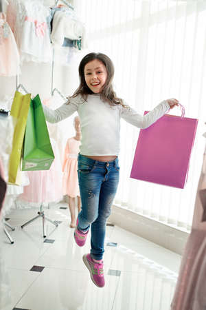 cute little girl on shopping. portrait of a kid with shopping bags. child in dress, sunglasses and shoes near shopping mall having fun. shopping Standard-Bild - 104976686