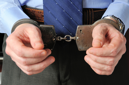 Man holds his hands in handcuffs before itself photo