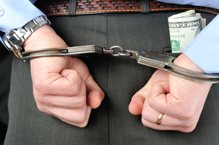 Man's hands in handcuffs and money in trouser pocket photo