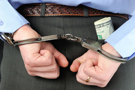 Mans hands in handcuffs and money in trouser pocket photo