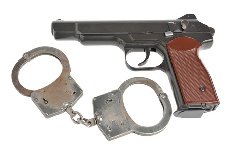 Pistol with handcuffs isolated on white background photo