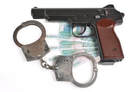 Pistol with handcuffs on money isolated on white background photo