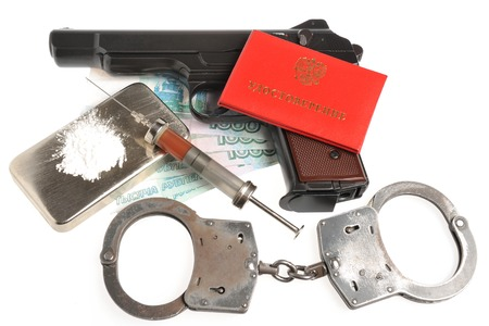 Drugs, syringe with blood, pistol, handcuffs,  identity document and money isolated photo