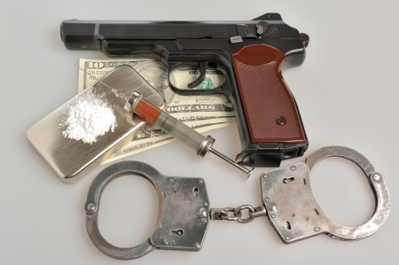 Drugs, syringe with blood, pistol, handcuffs and money on gray background photo